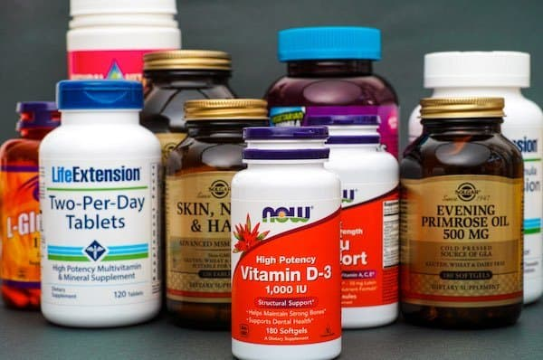 Bottle with Vitamin D3 by Now and some bottles with dietary supplement