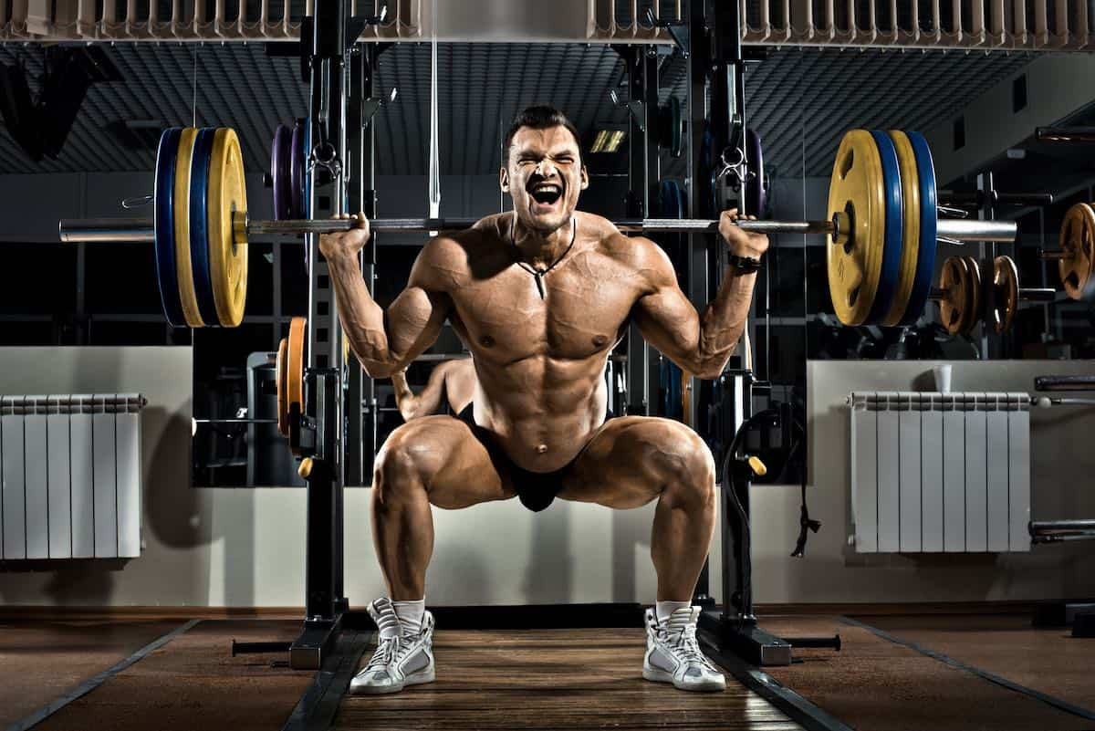 bodybuilder squating with olympic weights
